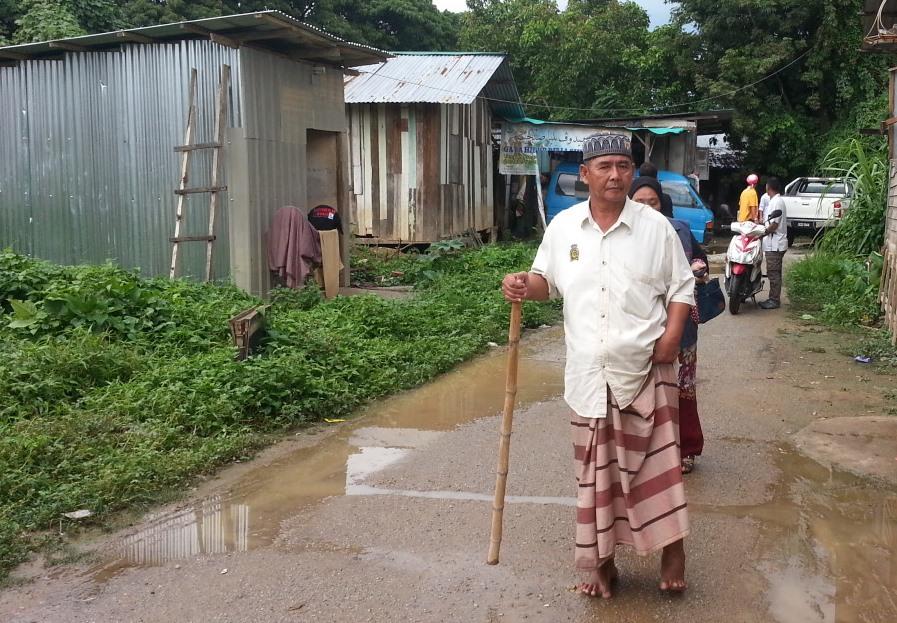 Hussin Gan berjalan kaki menggunakan bantuan tongkat dan berkaki ayam